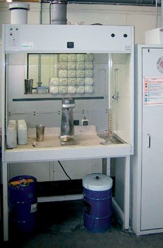 Combination of a hazardous material work station and a safety storage cabinet